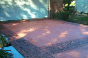 Concrete driveway finished in terracotta with London coble stone stamped border with charco release. Flushing, MI