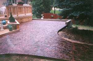 Stamped random stone pattern concrete patio finished in salsa red with a charco release. Flushing, MI