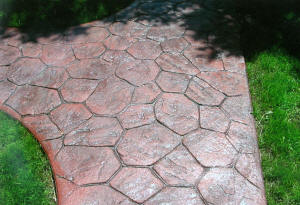 Stamped random stone pattern concrete walkway finished in brick red with a charco release. Swartz Creek, MI